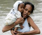 A mother cuddles her child while wading through floodwaters in Taytay township, Rizal province east of Manila, Philippines Friday Oct.2, 2009. (Marquez/AP)