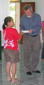 Dr. Neitzel receives a Haiti relief donation from children in Thailand church.